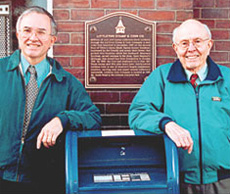[photo: David and Maynard Sundman in front of a plaque on Littleton's Opera Block]