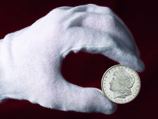 [photo: Coins should be held by their edges between thumb and forefinger.]