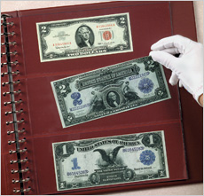 [photo: A large-size note is placed into a clear page of an archival-quality currency album.]