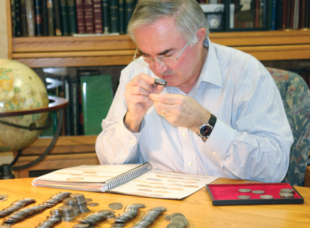 [photo: David examining a group of coins from this remarkable accumulation.]